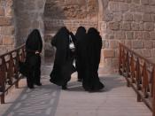 Four women clad in black, seen from the back, walking towards a stone gate in Bahrain.