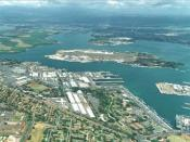 Aerial photograph of the Pearl Harbor Naval Base showing naval shore facilities in the foreground and Ford Island in the center.