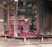 Original Description: Fabric merchant. Samarkand. Merchant's display includes silk, cotton, and wool fabrics as well as a few carpets. A framed page of the Koran hangs at the top of the stall.