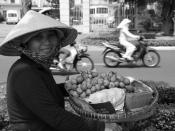 A Vietnamese woman with groceries in a basket