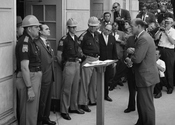 Attempting to block integration at the University of Alabama, Governor stands defiantly at the door while being confronted by Deputy U.S. Attorney General .