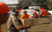 English: USAID packages are delivered by United States Coast Guard personnel.