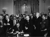 President Lyndon B. Johnson signs the 1964 Civil Rights Act as Martin Luther King, Jr., and others, look on.