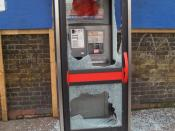A telephone booth with smashed tempered glass in Holloway, London.