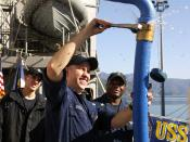USS Leyte Gulf Sailor attaches a pipe for supplying water to the ship.