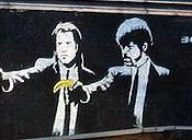 Image of London mural painted by Banksy, derived from the film Pulp Fiction (1994), showing Vincent Vega (John Travolta) and Jules Winnfield (Samuel L. Jackson) in a spoof of their well-known pose—Banksy depicts them pointing bananas rather than guns as i
