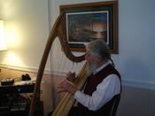English: A musician playing a harp.