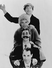 Marx Brothers, head-and-shoulders portrait, facing front. Top to bottom: Chico, Harpo, Groucho and Zeppo.