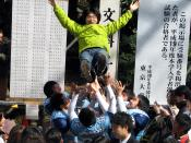 At Tokyo University at the announcement of test results, a successful student being thrown into the air in celebration