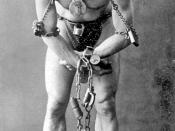 Harry Houdini, full-length portrait, standing, facing front, in chains