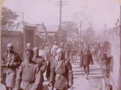 English: Company of Boxers, Tien-Tsin, China. Group of men walking down street.