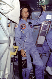 English: On Challenger's middeck, Mission Specialist (MS) Sally Ride, wearing light blue flight coveralls and communications headset, floats alongside the middeck airlock hatch.