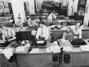 English: New York, New York. Newsroom of the New York Times newspaper. Reporters and rewrite men writing stories, and waiting to be sent out. Rewrite man in background gets the story on the phone from reporter outside.