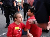 English: An Arlington County, Virginia police officer speaks to activist Mary Grant during a civil disobedience action during a UNITE HERE picket, explaining that if she does not leave the street, she will be arrested.
