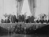English: Calvin Coolidge, Herbert Hoover, and Frank B. Kellogg, standing, with representatives of the governments who have ratified the Treaty for Renunciation of War (Kellogg-Briand Pact), in the East Room of the White House.