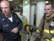 US Navy 060526-N-9851B-007 Engineering Training Team (ETT) leader, Master Chief Engineman Kevin Colligan, discusses the performance of fire teams involved with fighting a simulated fire in the number two auxiliary machine room