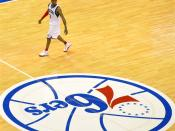 Allen iverson of the Philadelphia 76ers next to the team logo on the center circle at the Wachovia Center.