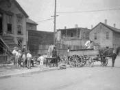 English: three African American men moving furniture with a horse and wagon while young Caucasian boys stand nearby on the sidewalk in front of a house watching in Chicago, Illinois.