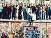 People atop the Berlin Wall near the Brandenburg Gate on 09 November 1989