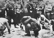 Austrian Nazis and local residents observe Jews forced to get on their hands and knees and scrub the pavement.
