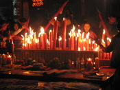 On Chinese New Year's Eve in Meizhou. Fireworks are set off to ward off the bad spirits from the previous year and welcome the new year in. Candles and incense are also lighted during prayers, like this scene on Chinese New Year's Eve.