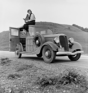 English: Dorothea Lange, Resettlement Administration photographer, in California. The car is a 1933 Ford Model C, 4 door Wagon. The camera is a Graflex 4x5 Series D.