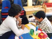 English: A special education teacher assists one of her students.