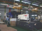 English: A 1300 ton injection molding machine with robotic arm. Location: Bekasi, Indonesia