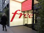 A woman walks past French internet service provider and mobile phone operator Free store in Paris