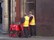English: Two Postmen on Balloon Street Perhaps chatting about the state of the post office and rumours of government sell-off to the private sector. These guys, with their modern trolleys, look old enough to remember the better days.