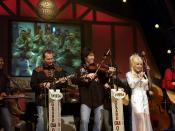 English: Country star Dolly Parton sings on stage during a Grand Ole Opry live broadcast in Nashville, Tenn., April 23 as U.S. soldiers watch the show via a video feed in Iraq. Español: Dolly Parton cantando en el programa televisivo Grand Ole Opry.