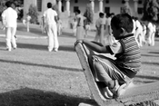 English: Street photography - photograph of a child watching children play on the grounds of Arts College at Osmania University, Hyderabad, AP - India.