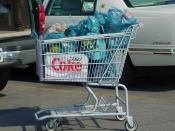 A shopping cart filled with bagged groceries located in a parking lot