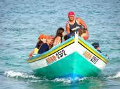A group of people riding a wooden boat off a beach in Venezuela.
