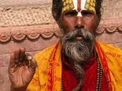 English: Nepali sadhu performing a blessing. Français : Sadou à Kathmandu Nepal avril 2004 Norsk (nynorsk): Heilag mann i Katmandu i Nepal, med pannemerke, symbolmønstra klede, rosenkrans rundt halsen og handa forma i ein mudra.