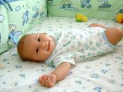 A smiling baby lying in a soft cot (furniture).