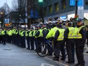 English: A line of RCMP officers on foot with mounted officers behind