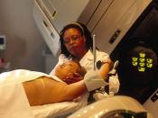 English: An Hispanic woman is being prepared for radiation therapy by an African-American female radiation therapist. The patient is placed in various positions. This is one of a series of six photos. Reuse Restrictions: None - This image is in the public