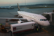 A Star Alliance-branded Air New Zealand aircraft parked at Melbourne Airport with an Alpha Flight Services trunk.