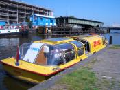 English: The world's first ever floating express distribution center in Amsterdam does the work of five DHL vans and saves over 3,000 liters of fuel a year. Русский: Судно почтовой компании DHL на канале в Амстердаме возле Центрального Вокзала