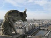 View west over the city of Paris from the Galerie des Chimères of Notre-Dame de Paris. One of the famous gargoyles (chimères) of the cathedral can be seen at the left of the photograph. The River Seine is visible at the bottom of the photograph. The neare