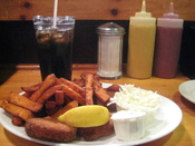English: Crab cakes, sweet potato french fries, cole slaw, tartar sauce, Coca-Cola and a wedge of lemon served at Bartley's in Harvard Square, Cambridge, United States.
