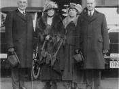 Hardings and Coolidges - The President and Vice-President of the United States with their wives, standing in front of automobiles. Left to right: President Warren G. Harding, hat in hand, with walking stick; First Lady Mrs. Florence Harding in fur coat an