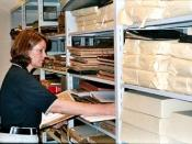 Used with the permission of the archivist pictured, Cyndi Shein. An Archivist surveying an unprocessed collection of materials. Surveying is commonly done to determine priorities for preservation and/or conservation of materials before an archivist begins