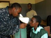 US Navy 100407-N-4657D-013 Hospital Corpsman 2nd Class Fitzroy Hall, an optometry technician assigned to a humanitarian civic assistance (HCA) medical team, examines a patient during an Africa Partnership Station West community