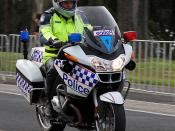 English: Victoria Police motorcycle policeman on a BMW R1200RT motorbike patrolling the course as an escort vehicle ahead of riders at the 2010 UCI Road World Championships Elite Men's time trial. Melbourne (Geelong), Victoria, Australia.