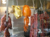 A variety of foods hanging from the window of a grocery store in Chinatown, San Francisco.