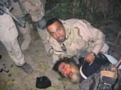 English: Iraqi-American, Samir, 34, pinning deposed Iraqi leader Saddam Hussein to the ground during his capture in Tikrit, on Saturday July 24, 2004. Samir was the translator for the U.S. Special Forces that helped find Hussein and pull him from his hidi