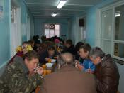 Homeless people are served food in one of the rooms of the