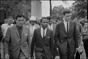walking to class at University of Mississippi, accompanied by U.S. marshals. According to http://hdl.loc.gov/loc.pnp/cph.3c35515, the men flanking Meredith are U.S. Marshal James McShane (left) and of the Justice Department (right)